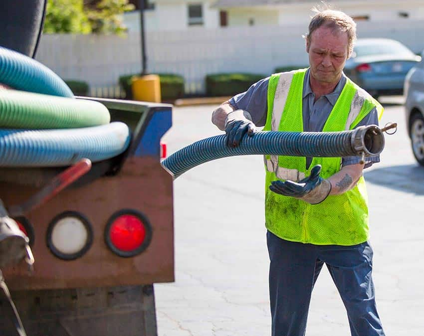Johnson Johns serviceman working septic hose in Northwest In
