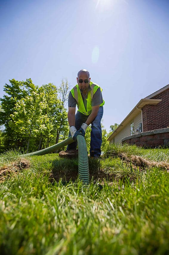 Septic system serviceman feeds a hose into a septic tank. Septic Services in St. Joseph County