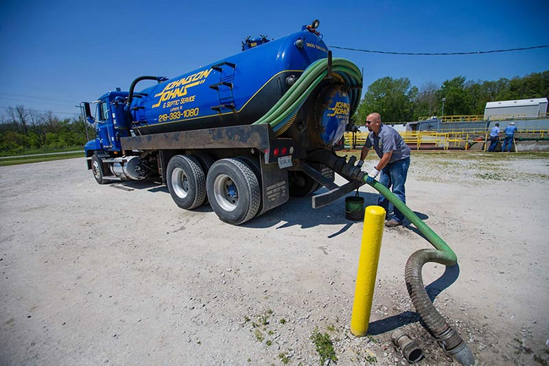 Johnson Johns truck and worker handling septic pump - Chesterton Septic Services, Valparaiso Septic Services