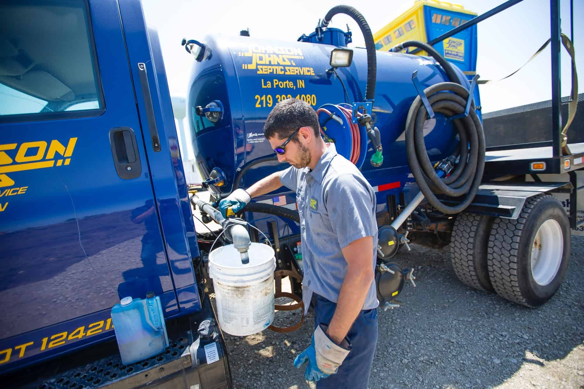 Johnson Johns employee filling a bucket on the side of his truck - Michigan City Septic Services, New Carlisle septic services